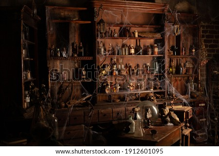 Halloween background Shelves with alchemy tools Skull spiderweb bottle with poison candles Witcher workspace Scarry room