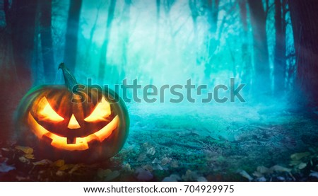 Halloween background. Spooky forest with dead trees and pumpkin.Halloween design with pumpkin #704929975