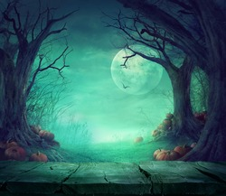 Halloween background. Spooky forest with dead trees and pumpkins and wooden table. Wood table. Halloween design with pumpkins