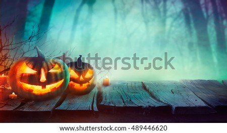 Halloween background. Spooky forest with dead trees and pumpkins.Halloween design with pumpkins #489446620