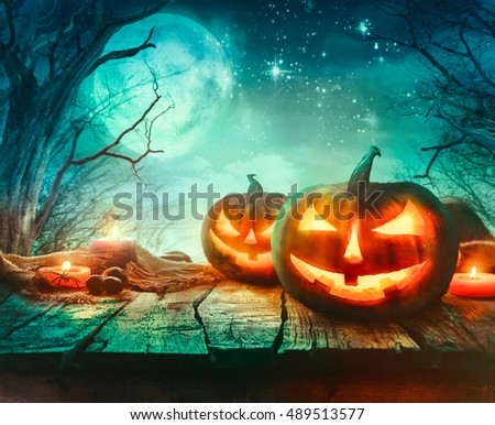 Halloween background. Spooky forest with dead trees and pumpkins.Halloween design with pumpkins #489513577