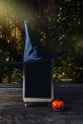 Halloween background. Spooky pumpkin, Witch hat, chalkboard on wooden floor with moon and dark forest. Halloween design with copyspace