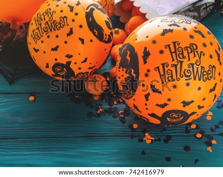 Halloween balloons and decorations on dark rustic wooden background. Wishing happy holiday - Shutterstock ID 742416979