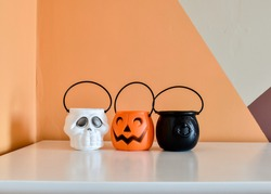 Halloween baskets on a table in the shapes of a skull, a pumpkin and a cauldron. Behind them, the wall has a geometric painting.