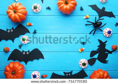 Halloween bats with pumpkins on blue wooden table stock photo
