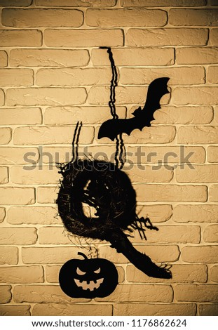 Halloween black bat, pumpkin and nest silhouette paper cutouts on beige brick wall. Holiday celebration symbols. Mystery and superstition concept. #1176862624