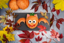 Halloween burger (sandwich) of sesame bun, sausage or ham, cheese, tomato ketchup, eggs, olives and parsley. bat.  Food kids. The concept of the celebration. Autumn leaves on a gray background