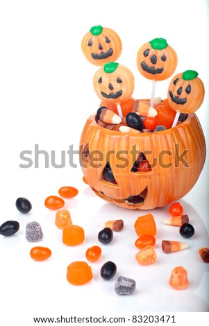 Halloween candy scattered around and in a pumpkin shaped bowl