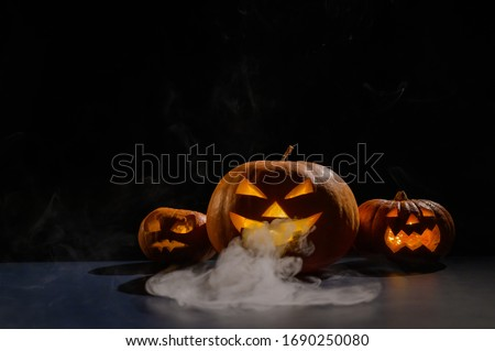 Halloween card. jack o lantern with candles glow on a black background. A row of creepy pumpkins with carved grimaces smokes in the dark.