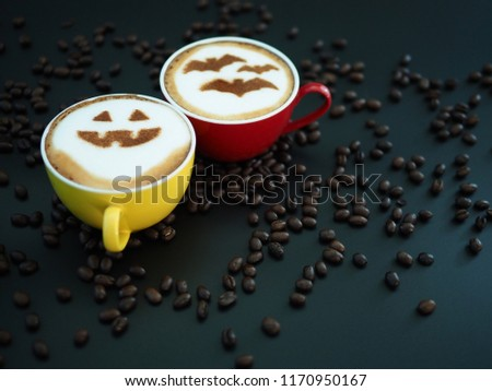 Halloween celebrated coffee concept coffee cup with halloween pumpkin face and symbolism of bats on frothy surface over dark background with coffee beans. Holidays food and drink art creative image. #1170950167