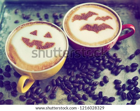 Halloween celebrated coffee cups with halloween pumpkin face and symbolism of bats on frothy surface over grey cement background with coffee beans. Holidays food and drink concept. (top view) #1216028329