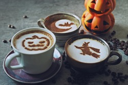 Halloween celebrated coffee cups with halloween witch, pumpkin face, moon and bat on frothy surface over grey cement background with coffee beans. Holidays food and drink concept. (selective focus)