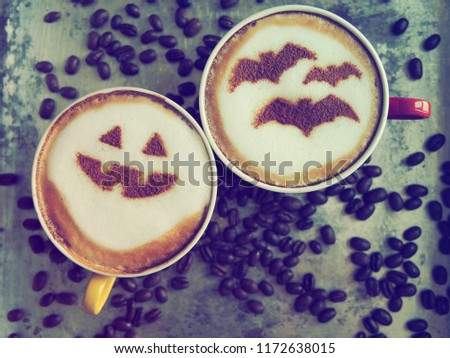 Halloween celebrated concept coffee cups with halloween pumpkin face and symbolism of bats on frothy surface over grey background with coffee beans. Holidays food and drink creative image. (top view) #1172638015