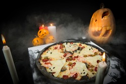 Halloween celebration party. ghost pizza served on delivery box. Bat, spiders, candles and painted pumpkins decor. Spider web on takeout pizza box. Horror creative food concept with fume on background