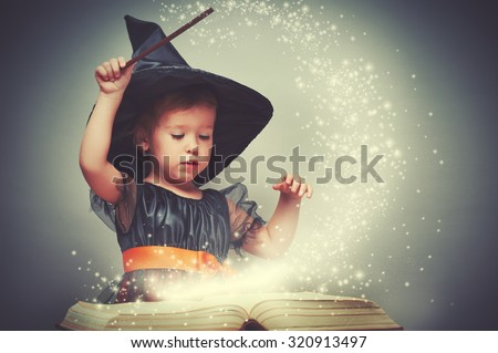 Halloween. cheerful little witch with a magic wand and glowing book conjure and laughs. Stock photo ©