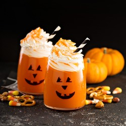 Halloween cold pumpkin cocktail or drink with jack o'lantern face and whipped cream