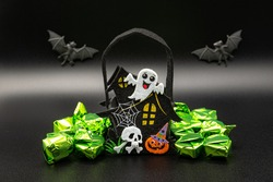 Halloween composition set with Candy Bags Cute Felt Pouches with Handles, Trick or Treat Goody Bags witch bewitched House, ghost, web and skull, bats on black background.