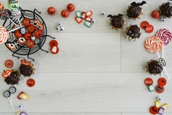 halloween composition with candies, chocolate, sweets and spider web, on wooden background