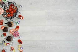 halloween composition with candies, chocolate, sweets and spider web, on wooden background on the left