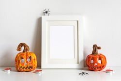 Halloween composition with ceramic pumpkins jack lantern and frame on table wall background. Greeting card template.