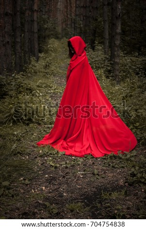 Halloween concept. A witch in a hoodie is red among the forest. Witchcraft and magic. Photo for your design. #704754838