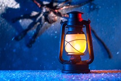 Halloween concept. Close up burning old oil lamp, monster in snow.