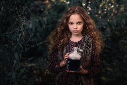 Halloween Concept! Cute little witch with a bottle of blue  smoking potion in the decorated garden.  Beautiful child girl in witch costume  with halloween decoration.