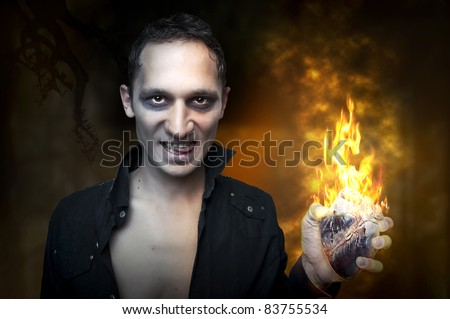 Halloween concept. Portrait of handsome man - night vampire, demon or zombie, holding in hand heart burn in fire
