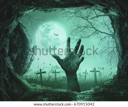 Halloween concept: Scary hand in cave stone on death tree with creepy cemetery background #670915042