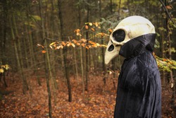 Halloween concept. Skull crow costume. Scary bird in the autumn forest.Horror and fear concept. man in white bird skull mask and black cloak. Autumn holidays time. halloween mood