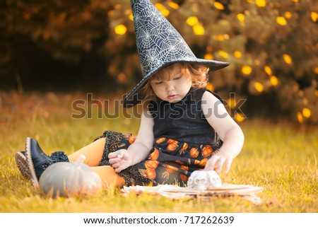 Halloween concept, toddler girl wearing witch hat and dress. Adorable little curl hair girl ready for trick-or-treat, autumn day
