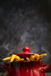 Halloween concept.Two Hen's paws with long nails manicured with black nail polish climb out of a steaming pan on old wooden table on black background with fog and smoke.