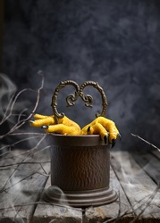 Halloween concept.Two Hen's paws with long nails manicured with black nail polish climb out of the well  on old wooden table on black background with fog and smoke. Selective focus.