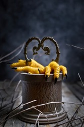 Halloween concept.Two Hen's paws with long nails manicured with black nail polish climb out of the well  on old wooden table on black background with fog and smoke.