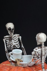 halloween concept - two skeletons drinking tea on pumpkin table against black background. Vertical image. Image contains copy space