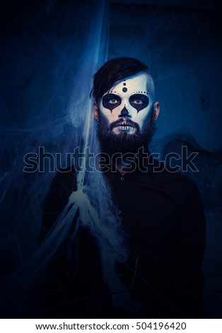 halloween concept with young man in day of the dead mask face art
