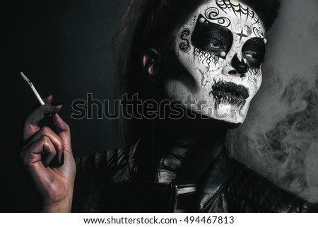 Halloween costume girl,Beautiful sexy brunette model woman.Look zombie. Creative make up.Halloween concept.Young woman in skull mask; face of a young woman in paper halloween mask;halloween concept