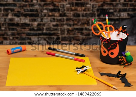Halloween Crafting with a spooky pencil cup and a blank sheet of yellow construction paper ready to be used. There is plenty of Negative Space for copywriting on the yellow paper and on the brick back