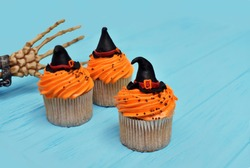 Halloween cupcakes. Witch hat cupcake. Halloween treats on wooden blue background with palm of the skeleton. Halloween background with copy space for text. Happy Halloween party. Monster party cupcake