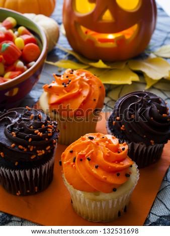 Halloween cupcakes with orange and black icing on orange napkin.