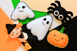 Halloween cute felt ornament decor. Small witch with broom, pumpkin head, two ghosts, spider. Halloween toys crafts on colored felt pieces. Simple kids sewing crafts concept. Top view