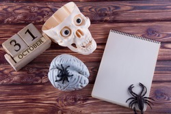 Halloween date on wooden cubes calendar. Plastic human skull, brain and spiders laying near blank paper notepad on table. Top view, copy space for text