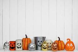Halloween decor display of Jack o Lantern candle holders on a shelf against a rustic white wood background. Copy space.
