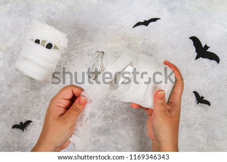 Halloween decor. Handicraft from a jar. Day Halloween.  Mummy from a jar and bandages and bats on a light table. The concept for Halloween. DIY.