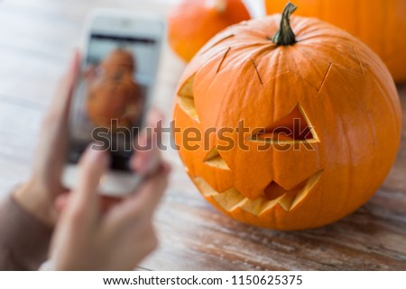 halloween, decoration and holidays concept - close up of jack-o-lantern or carved pumpkin and hands with smartphone