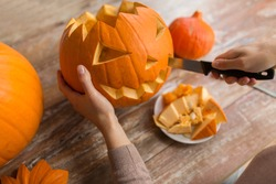 halloween, decoration and holidays concept - close up of woman with knife carving pumpkin or jack-o-lantern at home