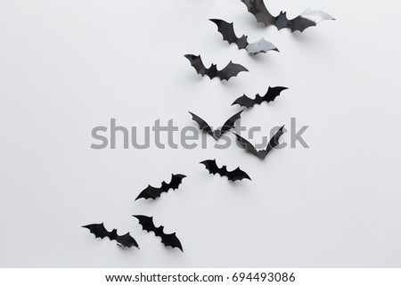 halloween, decoration and scary concept - black paper bats flying over white background