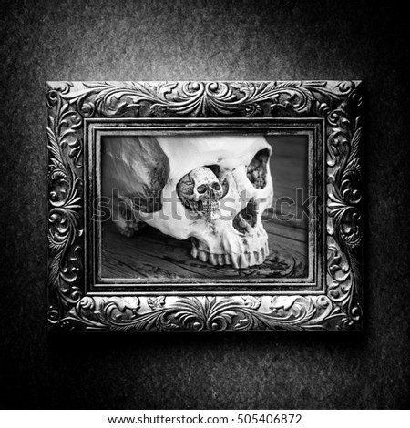 Halloween decoration with skull in silver vintage photo frame over grunge background, black and white
