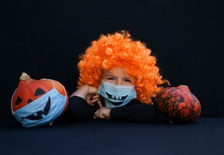 Halloween decorations and celebrations in  new reality of the COVID-19 pandemic. boy 4 years old in  orange wig and pumpkin. in  blue medical mask with a painted scary smile. On  black background