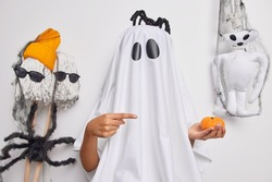 Halloween decorations and spooky holiday concept. Creepy ghost with black spider on head indicates at small pumpkin poses around scary toys isolated over white background. Mysterious creature